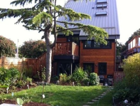 exterior of wood house with very high ceiling/roof with skylights and outdoor staircase, fenced yard with grass yard and shrubbery, Rental Suite in Contemporary Home in James Bay, Canada, pet friendly by owner vacation rental in Vancouver, Canada