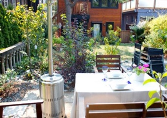 back yard of rental home with greenery and a dining table with chairs and outdoor heater, Rental Suite in Contemporary Home in James Bay, Canada, pet friendly by owner vacation rental in Vancouver, Canada